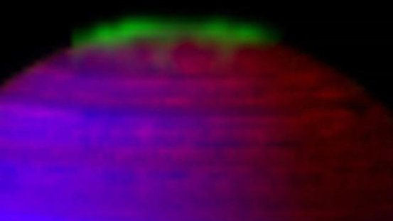 How is energy from Saturn's auroras redistributed from the poles toward the equator, and can it explain elevated temperatures in part of the planet's atmosphere?